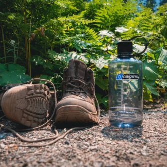 32 oz. Narrow Mouth bottle sitting on a dirt trail next to hiking boots