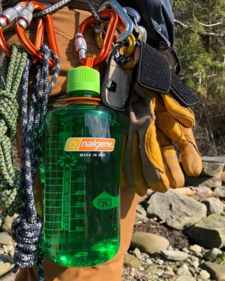 32oz Narrow Mouth Sustain Melon Ball attached to a clip on a hiker's backpack